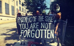 """People outside a prison with a musical instruments and a banner reading """"Prisoners of the state: You Are Not Forgotten"""""""