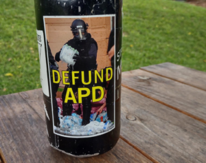 """""""Defund APD"""" sticker on a water bottle, depicting an asheville police officer stabbing and crushing water bottles after raiding a medic table during George Floyd protests in 2020"""